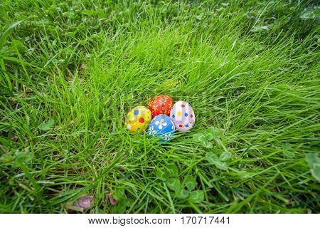Hand painted Easter eggs hidden on the grass ready for the easter egg hunt traditional play game. Top view.