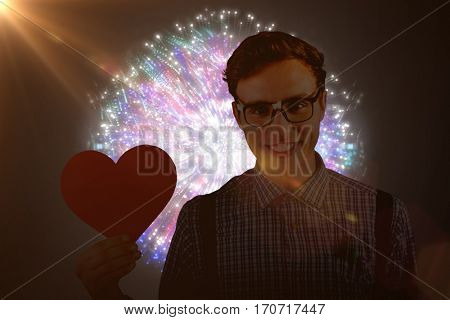 Geeky hipster holding a heart card against colourful fireworks exploding on black background