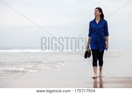 Young woman walking alone in a deserted beach on an Autumn day.
