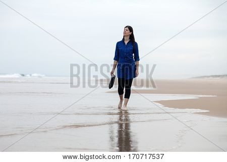 Young woman walking alone in a deserted beach reflected on the wet sand on an Autumn day.