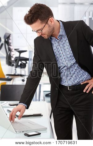 Confident caucasian business advisor at creative office working with laptop computer. Smiling, standing. wearing glasses.