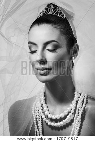 Black and white portrait of beautiful young bride eyes closed.