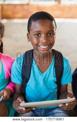 Portrait of smiling schoolboy using digital tablet at school