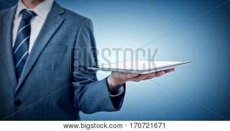 Midsection of businessman holding tablet computer against purple vignette