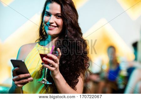 Portrait of beautiful woman using mobile phone while having red martini at bar