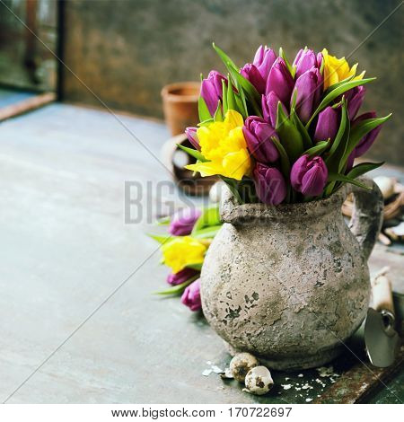 Beautiful spring tulips bouquet, easter eggs and garden tools on wooden table - spring, easter or gardening concept
