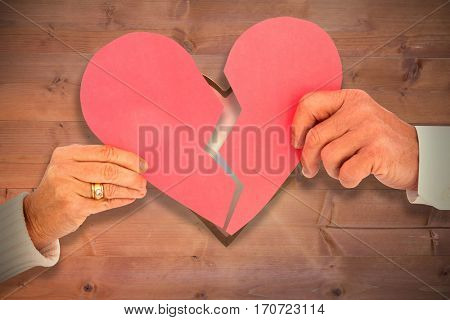 Couple holding a broken paper heart against heart in wood