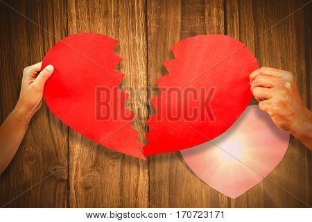 Cropped couple hands holding red cracked heart shape against heart in wood