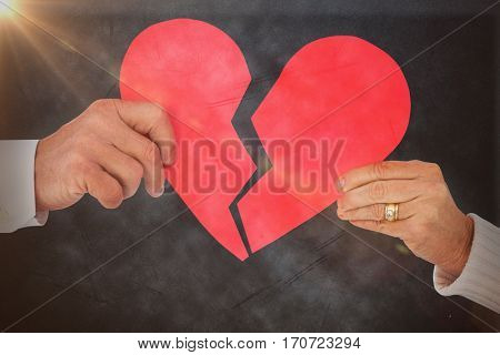 Couple holding a broken paper heart against grey