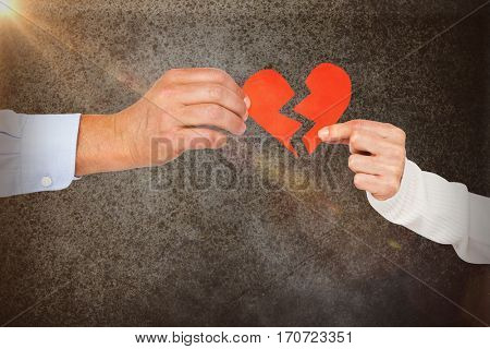 Couple holding broken heart shape paper against close-up of road surface