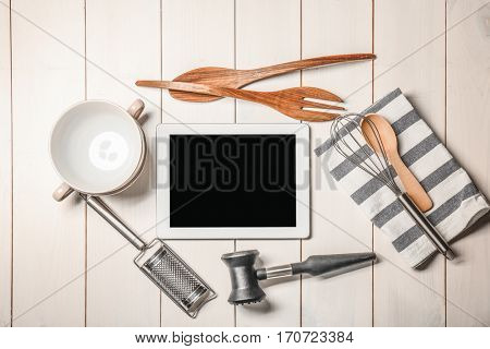 Kitchen utensils with tablet on wooden table