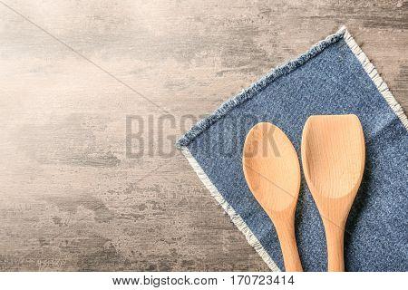 Wooden kitchen utensils with denim napkin on table