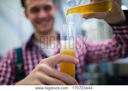 Close-up of brewer pouring beer in hydrometer cylinder at brewery factory