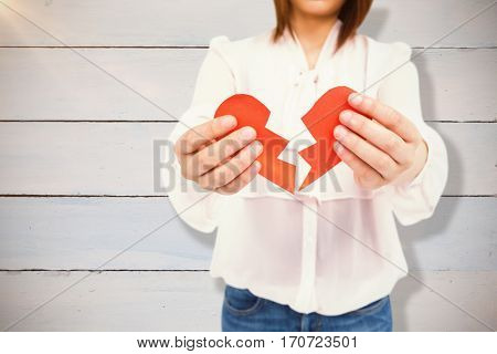 Woman holding broken heart paper against painted blue wooden planks