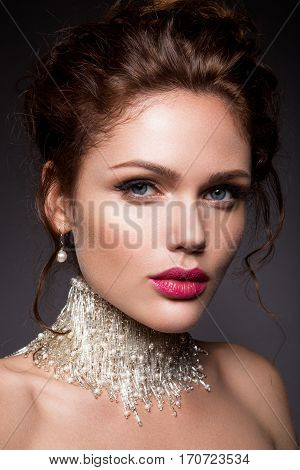 Glamour portrait of beautiful girl model with makeup and romantic wavy hairstyle. Fashion shiny highlighter on skin,  gloss lips make-up and dark eyebrows.
