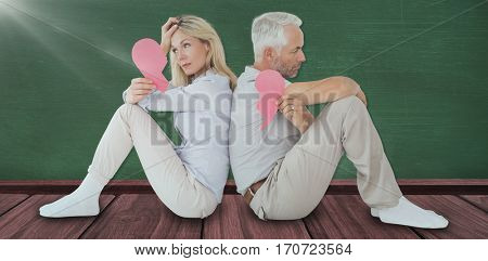 Unhappy couple sitting while holding broken heart against green room