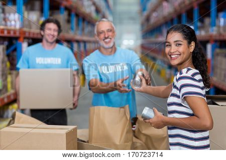 Focus of happy woman gives some goods to volunteers in a warehouse