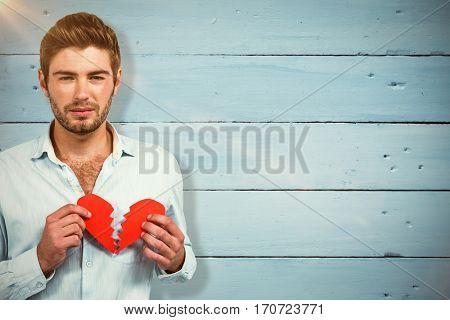 Sad man holding heart halves against painted blue wooden planks