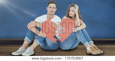 Young couple sitting on floor with broken heart shape paper against blue room