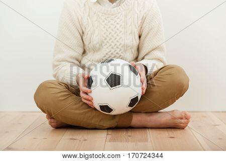 Barefoot Cross-legged Boy Holding A Soccer Ball