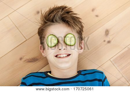 Laughing Young Boy With Cucumber On His Eyes