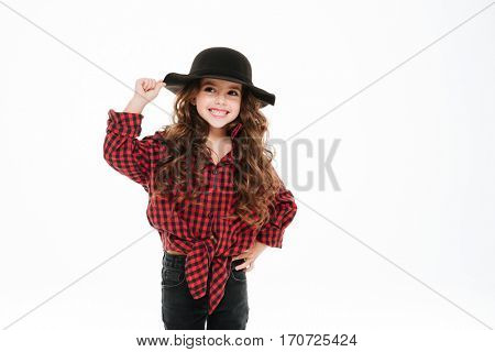 Smiling curly little girl in plaid shirt and hat standing over white background