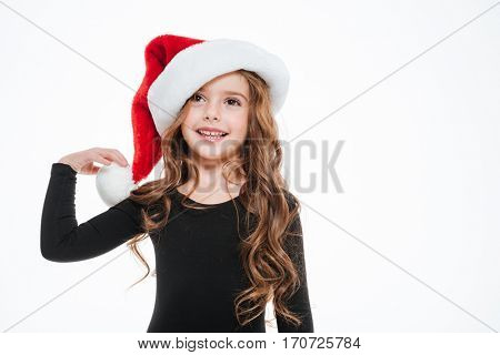 Happy pretty little girl in santa claus hat standing and smiling over white background