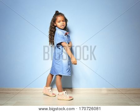 Cute little African American girl in denim shirt against blue wall. Fashion concept