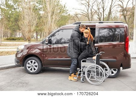 Young man helping handicapped woman to sit in wheelchair