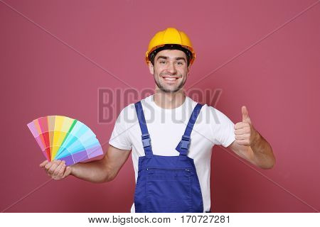 Handsome young decorator on color background
