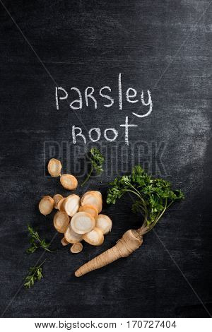 Top view photo of parsley root over dark chalkboard background.