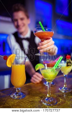 Male bartender holding cocktail glass at nightclub