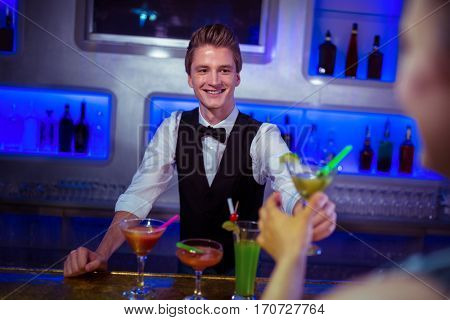 Smiling male bartender serving cocktail to woman at nightclub