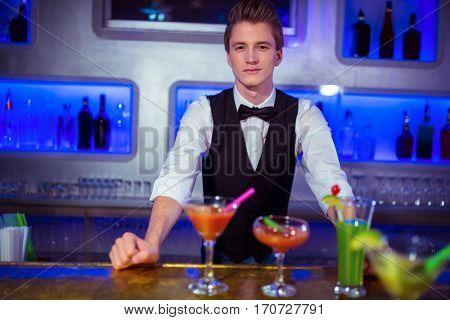 Portrait of confident male bartender standing at nightclub
