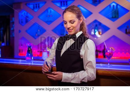 Young barmaid writing in notepad at counter in bar