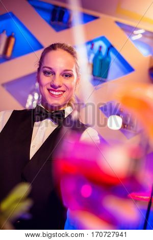 Portrait of happy beautiful barmaid standing at nightclub