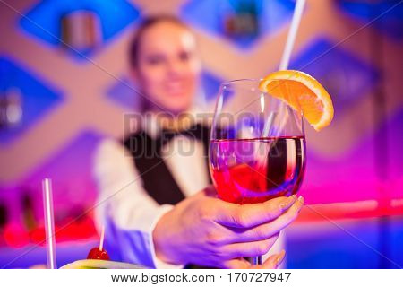Barmaid holding cocktail glass at nightclub