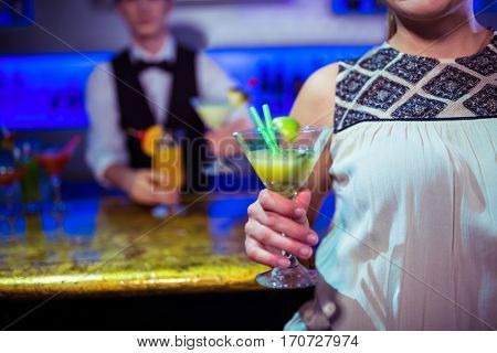 Woman with cocktail glass standing by bartender at nightclub