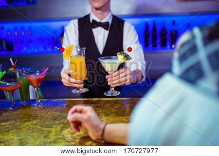 Bartender serving cocktail to woman at nightclub