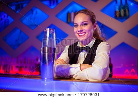 Portrait of confident young barmaid sitting by cocktail shaker at counter