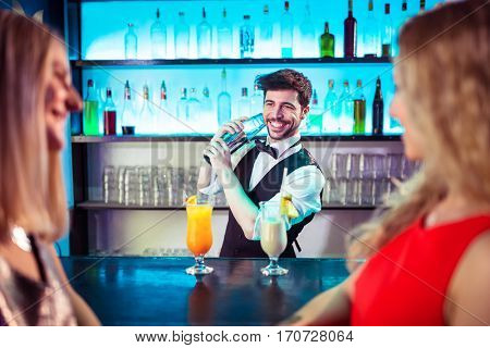 Barkeeper smiling while preparing cocktail for female customers at bar counter