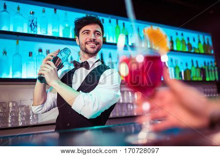 Barkeeper preparing cocktail for customer at bar counter