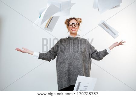 Tired stressed young woman in glasses throwing documents in the air