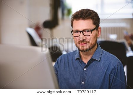 Portrait of confident male executive with computer at office