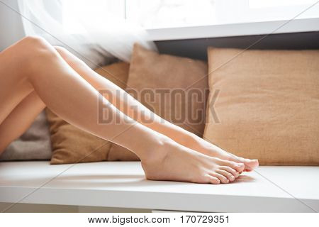Photo of woman legs near the window in bedroom. Cropped image