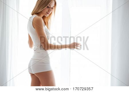 Sexy Woman standing near the window and looking down