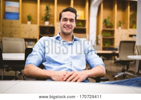 Portrait of confident young male executive sitting on chair at office