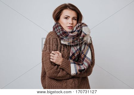 Woman in sweater and scarf freezes in studio. Isolated white background