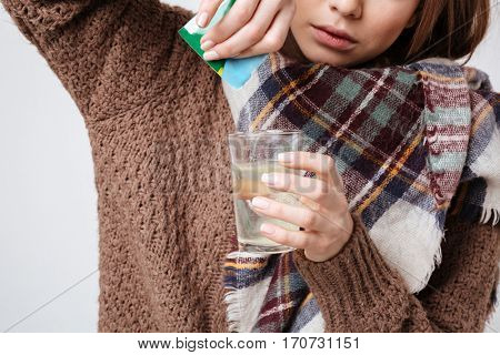 Cropped image of woman in sweater and scarf prepare medicaments in studio. Isolated gray background