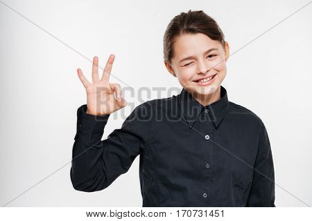 Photo of cheerful young girl posing and make okay gesture isolated over white background.